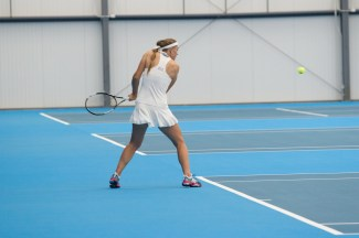 Sophomore Nina Khmelnitckaia from Moscow, Russia prepares to hit the tennis ball during a doubles match at Jayhawk Tennis Center on Jan. 20. Khmelnitckaia won both her doubles and singles matches of the night against Saint Louis. Ashley Hocking/KANSAN