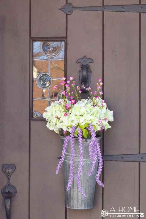 This spring floral door hanger is so easy to do and requires no floral arranging skills! A flower arrangement is a fun alternative to a wreath! Plus, I love the galvanized bucket!