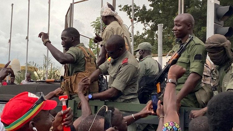 """Malian soldiers are celebrated as they arrive at the Independence square in Bamako on August 18, 2020. - Mali's Prime Minister Boubou Cisse called on August 18, 2020, for """"fraternal dialogue"""" with soldiers who seized a key military garrison and have triggered fears of a coup attempt.   The prime minister also admitted that the soldiers may have """"legitimate frustrations"""". Details of the events in Mali remain unclear. But according to witnesses and officials, soldiers seized an important army base in the town of Kati, near the capital Bamako, on the morning of August 18, 2020. (Photo by MALIK KONATE / AFP)"""