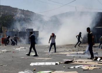 Los manifestantes palestinos buscan protección contra los gases lacrimógenos durante los enfrentamientos con las tropas israelíes. | EFE