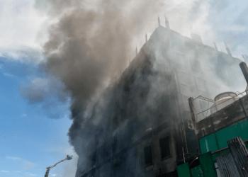 Los bomberos intentan apagar un incendio que estalló un día antes en una fábrica de bebidas y alimentos en Rupganj. Foto: AFP.