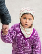 A young girl holds fast to her father's hand at the festival.