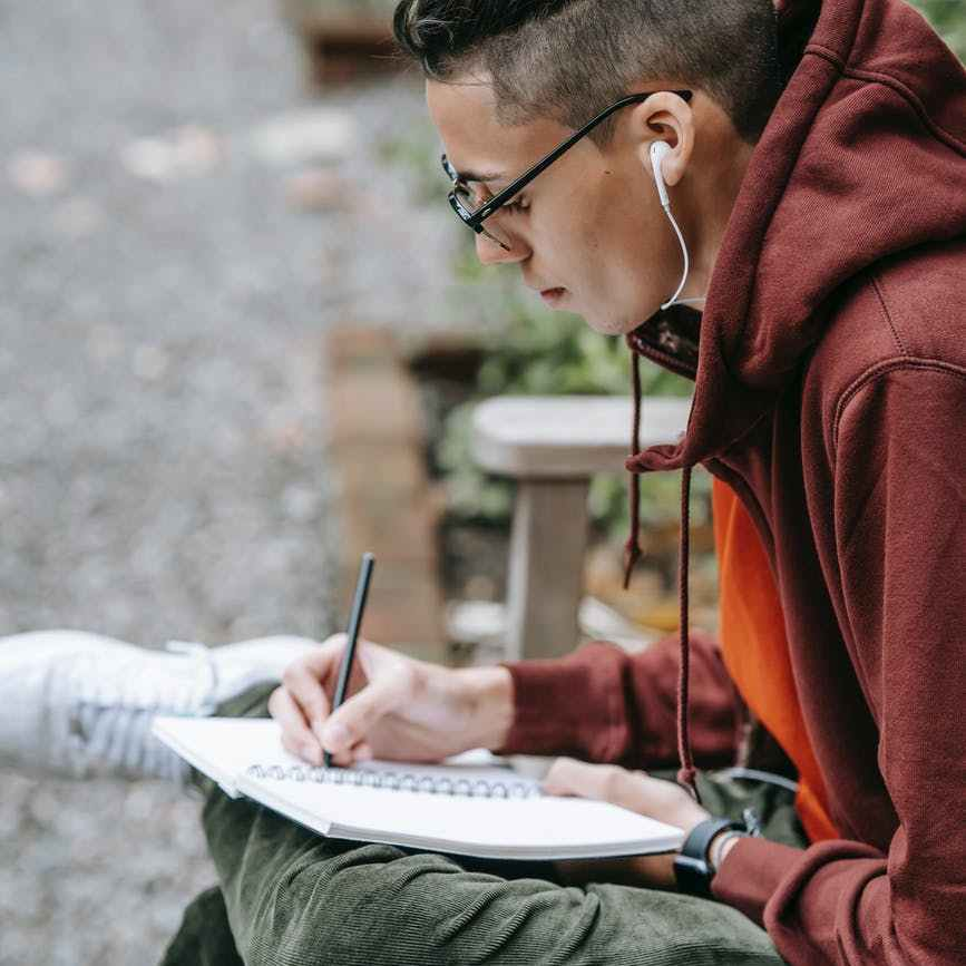 young student in hoodie and eyeglasses studying and taking notes
