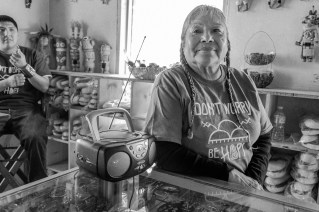 Janice Day listens to the radio at her store Tsakurshovi, where she sells traditional crafts to both tourists and locals. © Tomas Muscionico