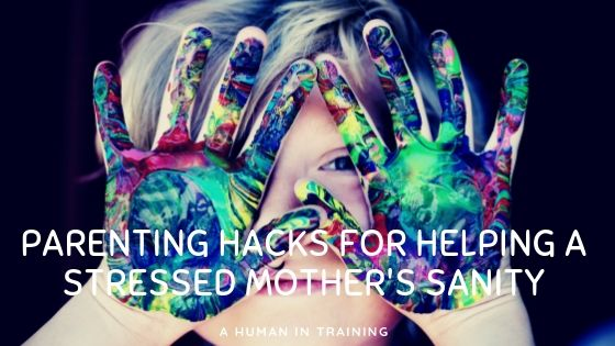 a young child with paint all over his hands, requiring the need of a parenting hack