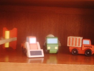 Some of his toys lined up on the shelf in the living room.