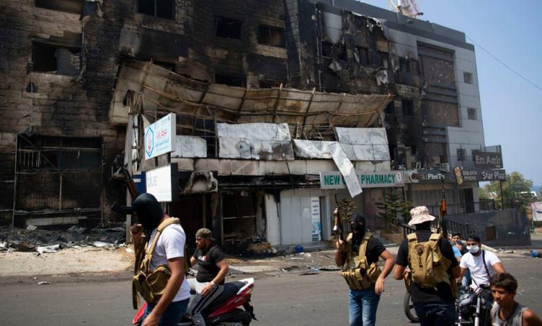 مسلّحون سنّة أمام مبنى أًضرمت فيه النيران في اشتباكات، خلال تشييع جنازة حسن زاهرغصن ، 14 عامًا. Photo Credit: AP