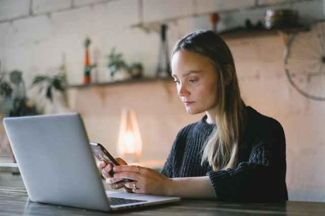 serious woman browsing smartphone near laptop