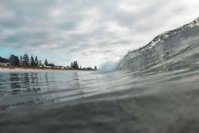 wavy ocean near coast under cloudy sky