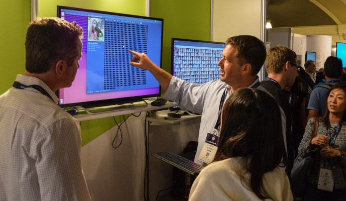 Joseph McKinney of NVIDIA walks an attendee through some of their software at their AI Summit booth