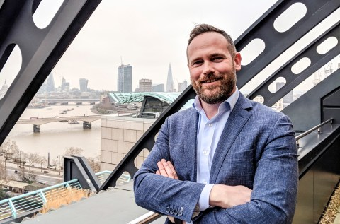 Rob McCargow, PwC UK's AI Programme Lead, standing on a rooftop overlooking central London.