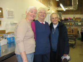 Sr. Carol visits with pantry volunteers, left to right, Pat Winking and Phyllis Brinkley.