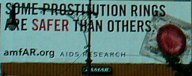 """A poster on West Side Highway depicting a condom, """"Some Prostitution Rings Are Safer Than Others""""."""