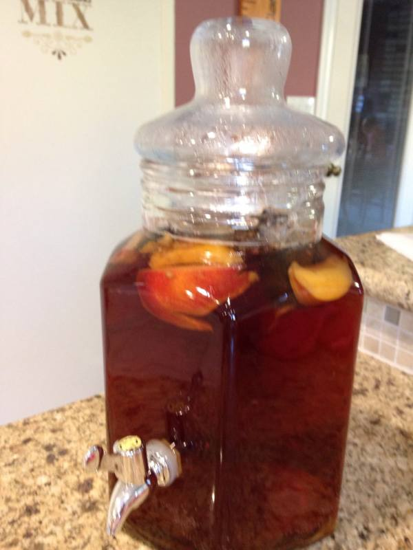 A fresh batch of nectarine-infused sun tea in a glass drink dispenser.