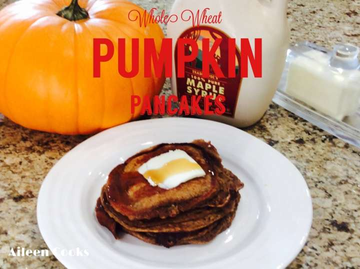 A stack of whole wheat pumpkin pancakes next to a pumpkin, bottle of maple syrup, and butter dish.