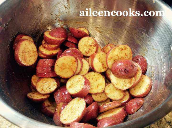 Sliced red potatoes tossed with olive oil and spices, ready to be transformed with the roasted red potatoes recipe.