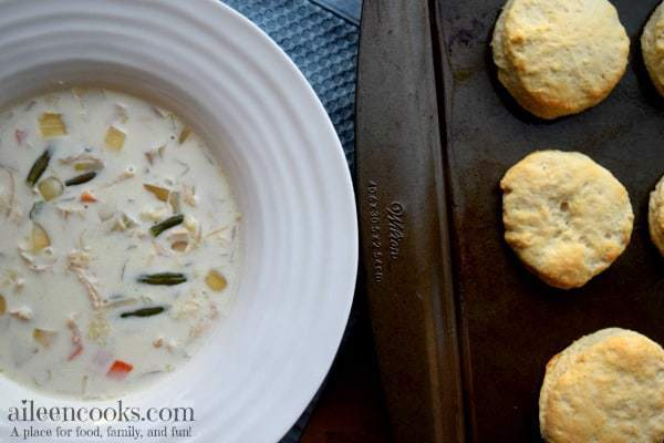Overhead shot of large bowl filled with creamy chicken pot pie soup next to a batch of biscuits.