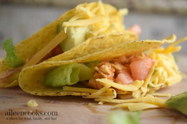 instant pot salsa chicken tacos in crispy taco shells with fresh tomato and lettuce