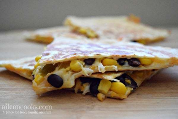 black bean and corn quesadillas cut into triangles with melting cheese dripping out.