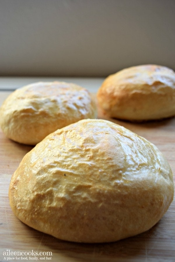 The completed Italian bread bowls recipe on a cutting board and ready to be served with soup or chili.