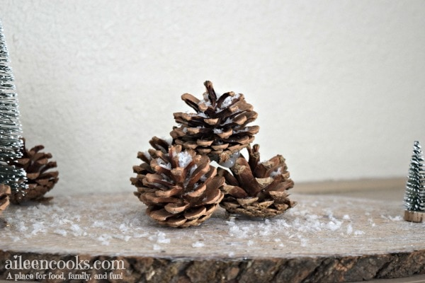 Create these festive and rustic winter centerpieces with wood rounds, sisal trees, pine cones, and craft snow!