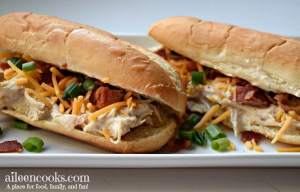 Close up of instant pot crack chicken on a roll with cheese, scallions, and bacon.