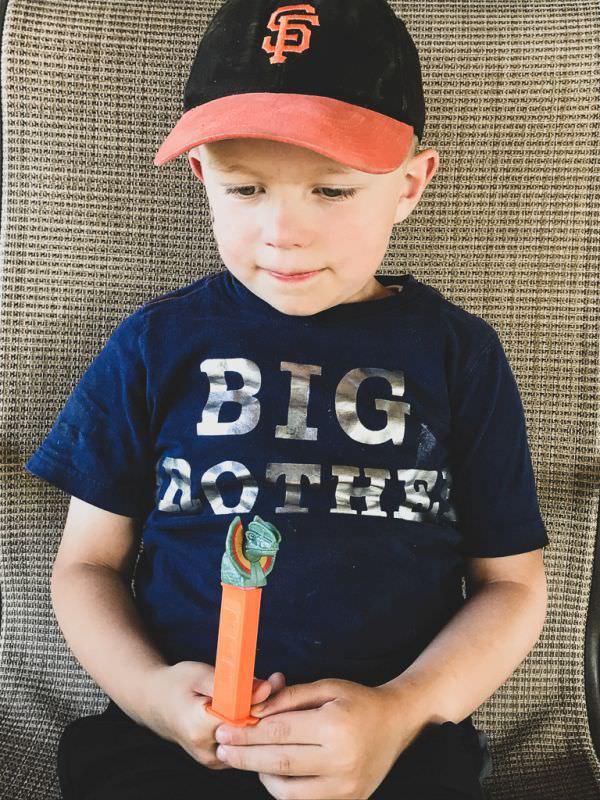 Boy holding Jurassic World Pez Dispenser.
