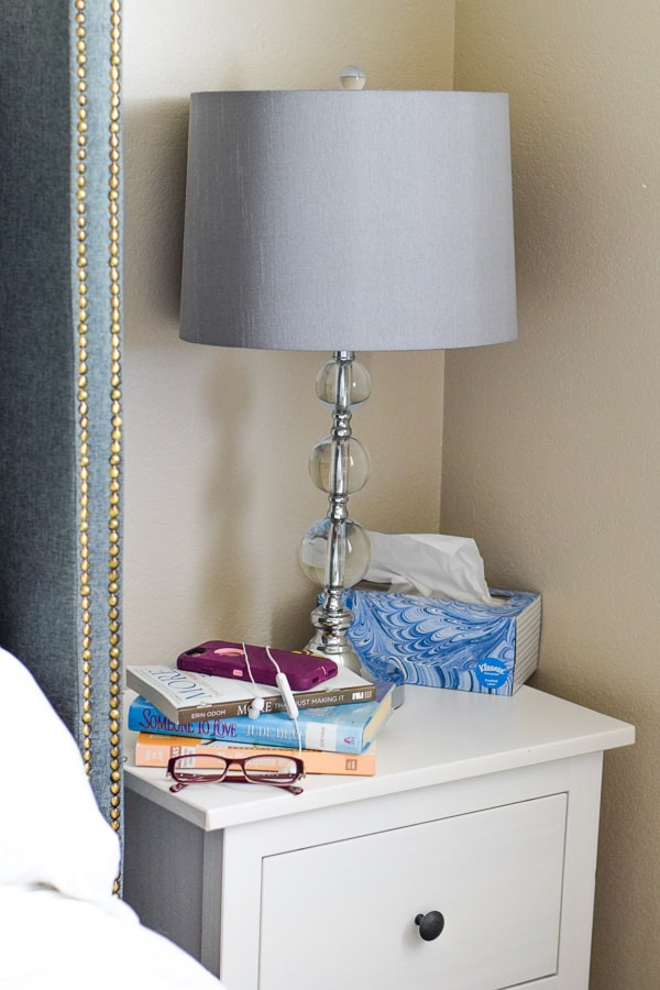 nightstand with books, glasses, and cell phone.