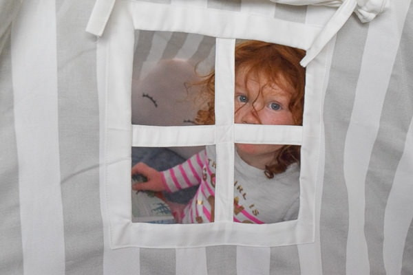 Little girl peaking through the window of her reading nookk.