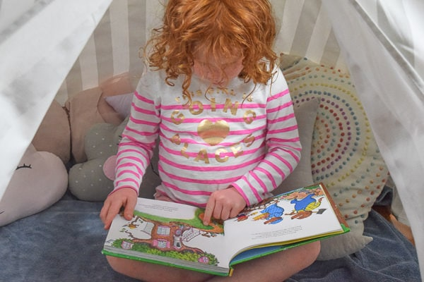 Little girl pointing to a picture in her book, sitting inside a reading nook.
