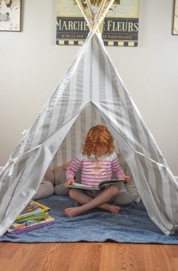 Little girl sitting in a cozy reading nook made of a teeppe.