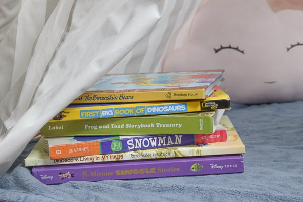 Stack of colorful books inside a reading nook.