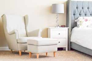 Grey wingback chair, white nightstand with grey lamp and grey bed bed with white floral bedding.