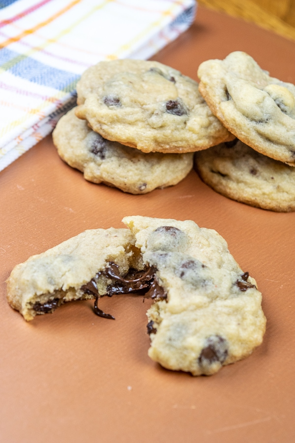 A salted chocolate chip cookie broken in half with the chocolate dripping out in front of a stack of cookies.