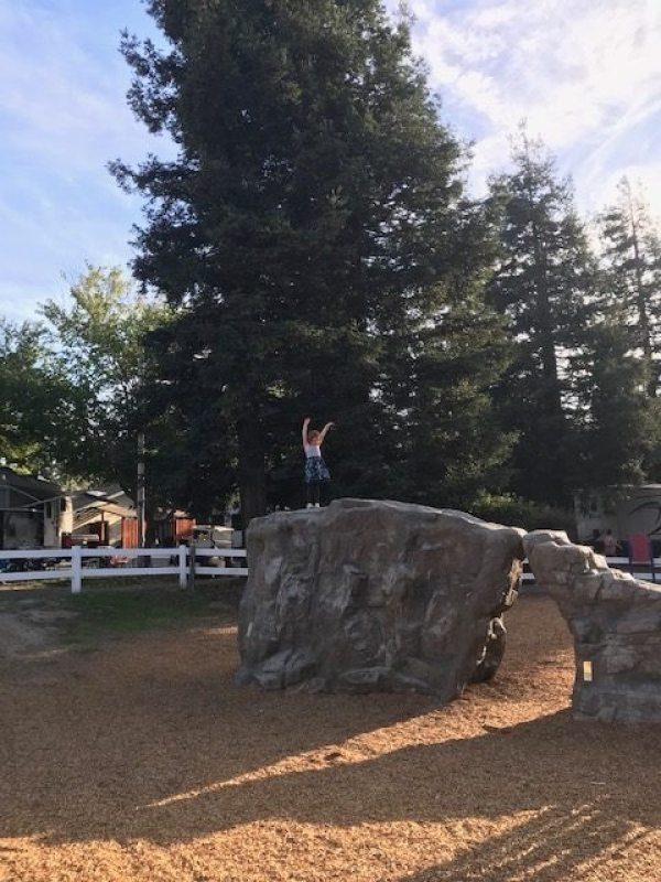 A 4-year-old-girl standing on a rock in the Petaluma KOA campground playground.