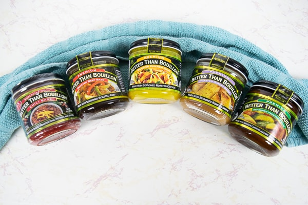 Several Better Than Bouillon flavors lined up on a blue kitchen towel.