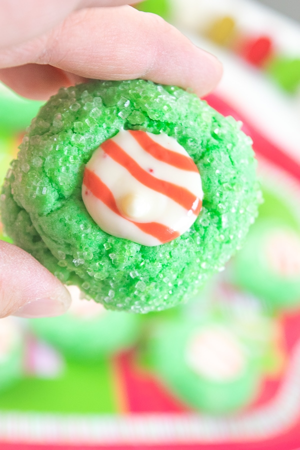 "Add these Grinch Christmas Cookies to your list this year! These sparkly green cookies have a kiss ""Santa hat"" in the middle making them look just like The Grinch Who Stole Christmas!"