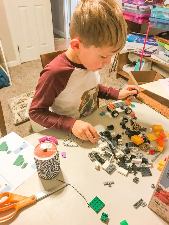 A little boy hard at work building LEGO.