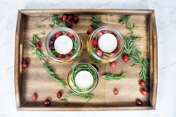 Mason jar christmas centerpieces arranged on a wooden serving tray.