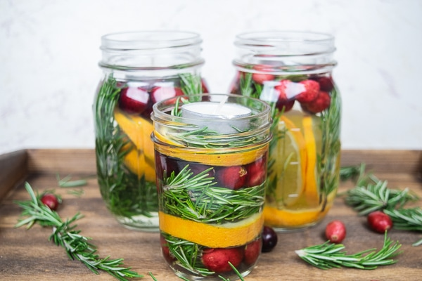 A side view of three mason jar Christmas centerpieces filled with cranberries and oranges.