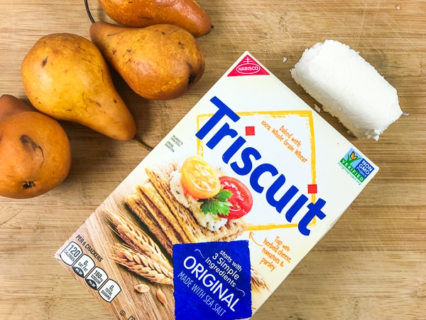 The three ingredients used to make goat cheese appetizers: honey flavored goat cheese, Triscuit crackers, and fresh pears.