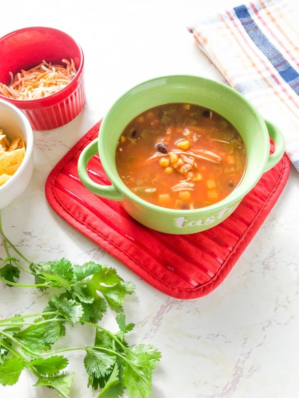 The finished instant pot chicken tortilla soup recipe show in a green soup bowl.