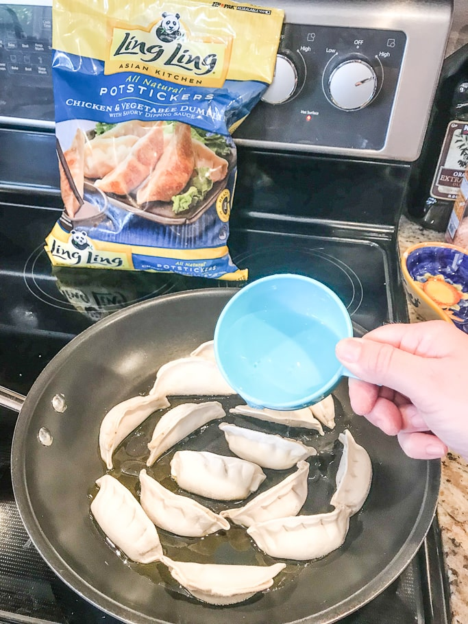 A cup of water being poured into a pan of frozen potstickers.