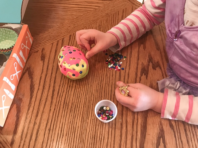 A child's hand decorating an egg made of clay.