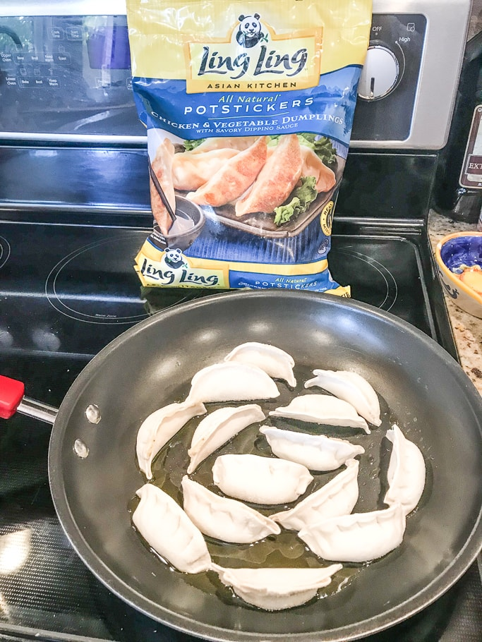 Frozen pot stickers in a large skillet.