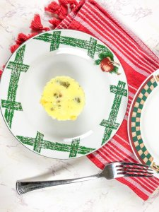 An instant pot egg bit on a white and green plate next to a red striped towel.