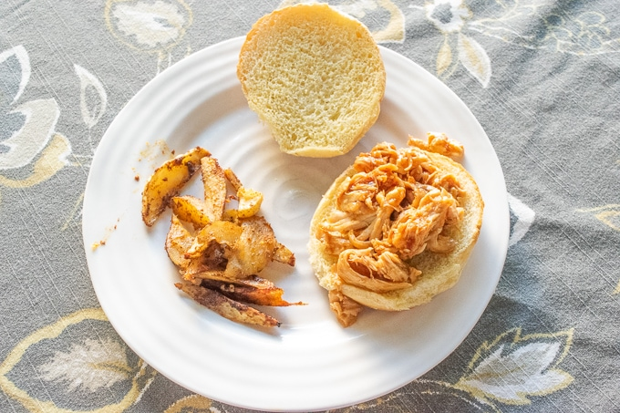 A plate of French fries and instant pot pulled chicken on a hamburger bun.