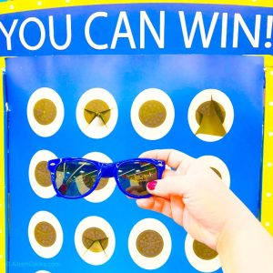 """A hand holding a pair of blue sunglasses in front of a blue and yellow game that says """"you can win""""."""