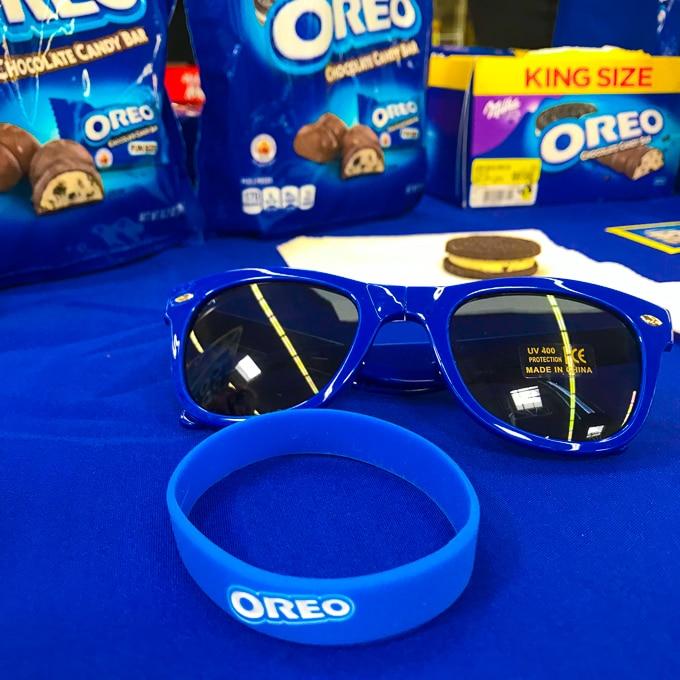 An OREO bracelet and sunglasses on a blue tablecloth.