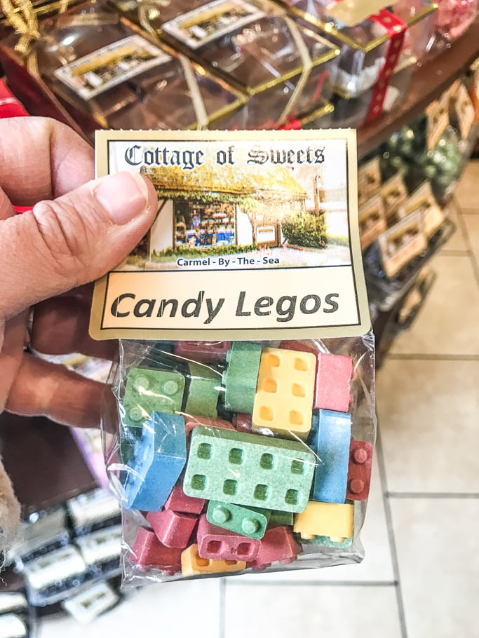A hand holding a bag of candy LEGOs at Cottage of Sweets.